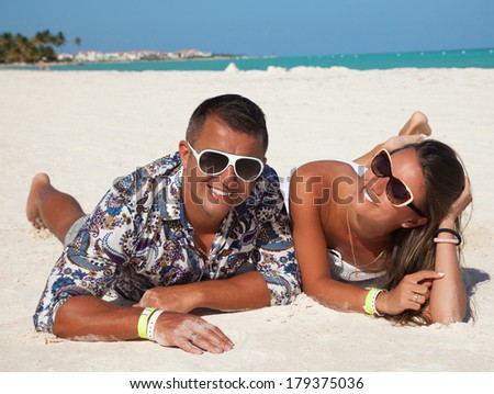 Fashion couple relax on a tropical beach at Cap Cana, Dominican Republic. Lovers dreaming and thinking looking happy, smiling cheerful. Outdoors, lifestyle. - stock photo