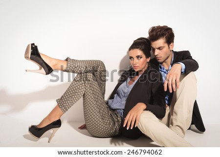 Fashion couple sitting on the floor together, looking away from the camera. The woman is leaning on ther man. - stock photo
