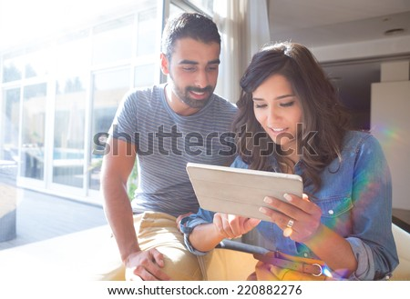 Fashion couple using a tablet with sunbeams and lens flare - stock photo