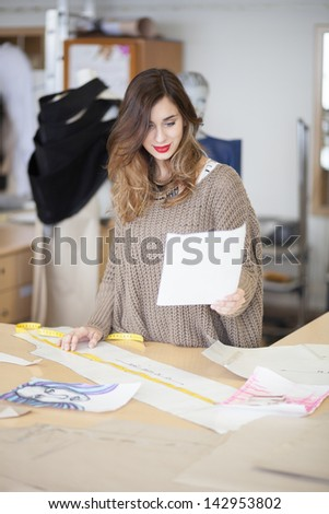 Fashion designer looking at dress design she drew - stock photo