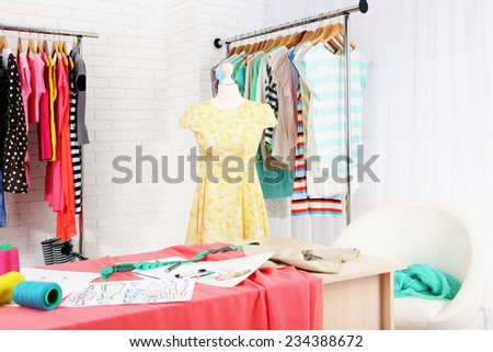 Fashion designer studio with professional equipment, sketches, mannequin, cloth - stock photo
