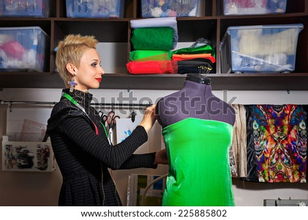 Fashion designer working with dummy and cloth - stock photo