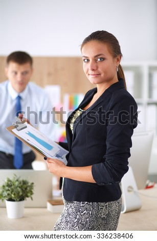 Fashion designers working in studio standing near desk
