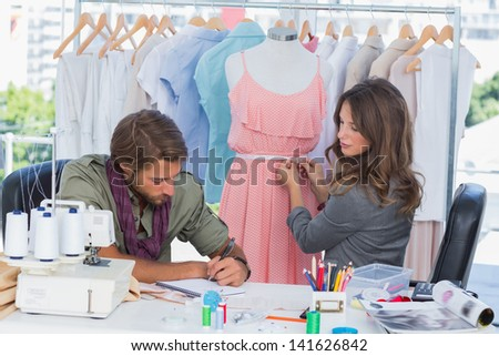 Fashion designers working together on a dress