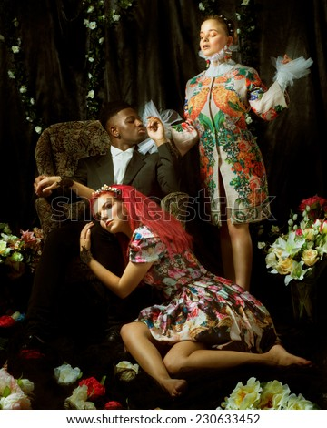 Fashion editorial with two women and one man between flowers - stock photo