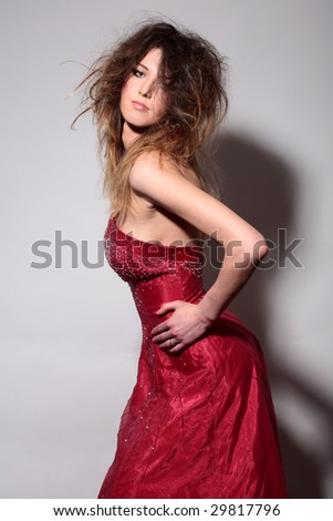 fashion elegant young woman in red dress on gray