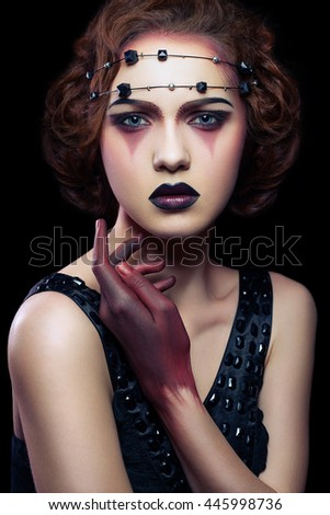 Fashion european model with unusual makeup and hairstyle and dress and red colored hand on black background.