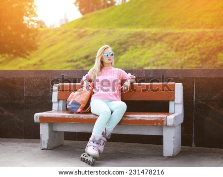 Fashion, extreme, youth and people concept - pretty stylish confident blonde in sunglasses with roller skates in the city park, cool roller girl outdoors - stock photo