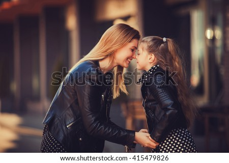 Fashion family concept - stylish mother and child wear. A portrait of a happy family: a young beautiful woman with her little cute daughter. - stock photo