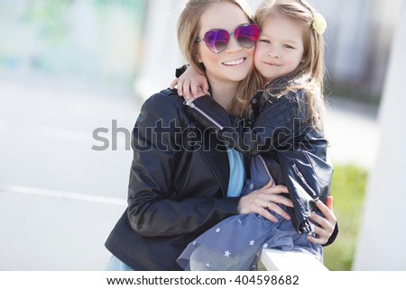 fashion family. woman with child girl in family fashionable look having fun outdoor. Fashion young mother and child daughter wearing a sunglasses - stock photo