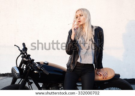 Fashion female biker girl. Young blonde woman sitting on vintage motorcycle and smoking cigarette. Outdoors lifestyle portrait - stock photo