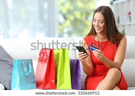 Fashion girl buying online with smart phone and credit card with colorful shopping bags beside - stock photo