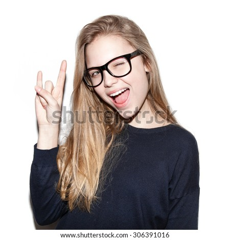 Fashion girl hipster giving the Rock and Roll sign . Pretty models smiling on white background, not isolated. Toned - stock photo