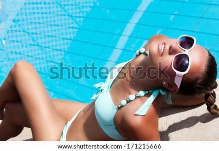 Fashion girl in beautiful bikini lying near swimming pool. - stock photo