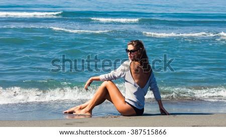 fashion girl in bikini and tunic  on sandy sunny sea beach, full body shot side view - stock photo