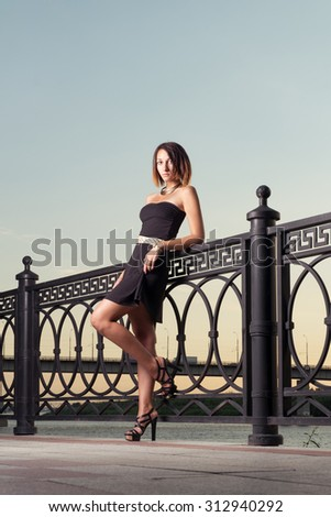 Fashion girl is standing on one leg, image toned. Fashionable brunette is posing leaned against metal fence in evening. Deep colorful evening sky is over her. Copy space. - stock photo