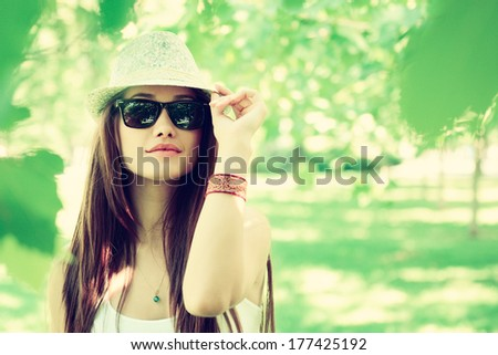 fashion girl outdoor portrait, young woman walking in summer park  in sunglasses and fedora with long brown hair, toned and noise added - stock photo