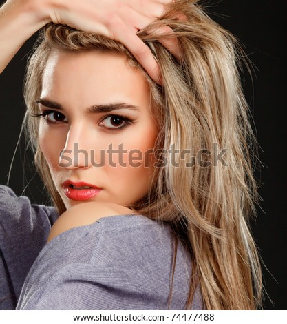 Fashion girl posing on dark background - portrait - stock photo