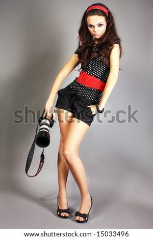 Fashion girl posing with camera on black background - stock photo