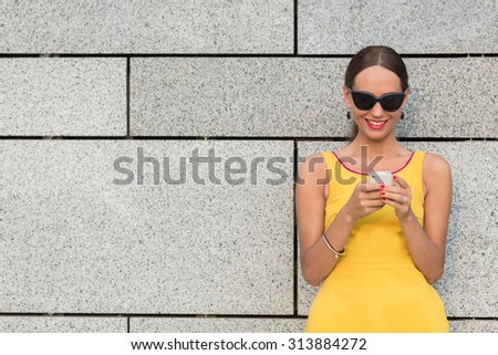 Fashion girl reading messages over mobile phone and smiling. Pretty lady in little yellow dress standing near brick wall and looking at screen. - stock photo