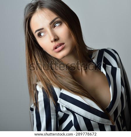 Fashion girl's portrait. Young sexy brunette woman posing at studio in striped jacket - stock photo