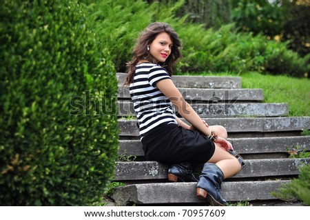 Fashion Girl sitting on stairs in park