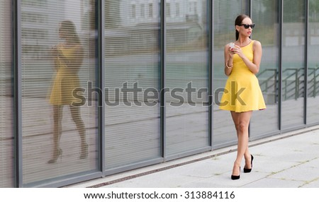 Fashion girl walking in the city and using her mobile phone. Pretty lady in little yellow dress wearing black high heels. - stock photo