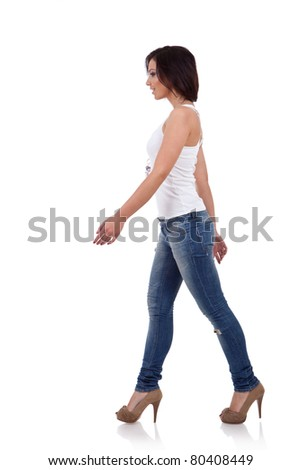Fashion girl wearing shirt and jeans walking in studio - stock photo