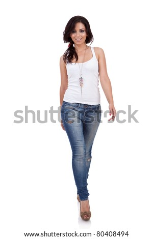 Fashion girl wearing white shirt and jeans walking in studio