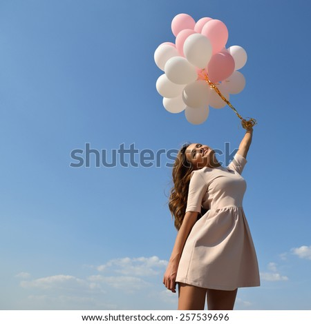 Fashion girl with  air balloons over blue sky - stock photo