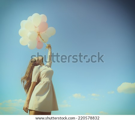 Fashion girl with  air balloons over blue sky, toned. - stock photo