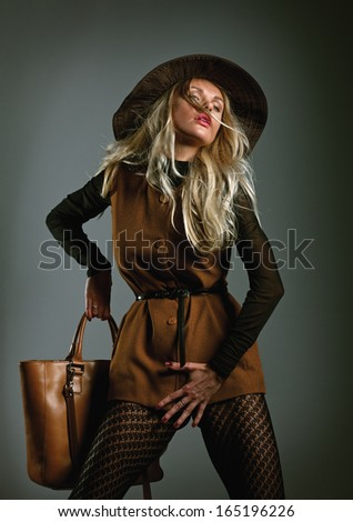 Fashion girl with bag posing in the studio.