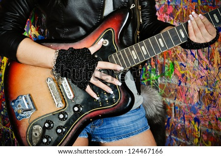 Fashion girl with guitar playing hard-rock - stock photo