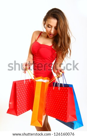 Fashion girl with shopping bags, looking into the open bag