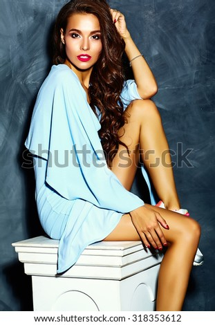 fashion glamor stylish beautiful  funny crazy young woman model with red lips in summer bright colorful hipster blue dress sitting on white colon near gray wall - stock photo