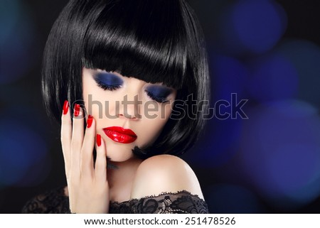Fashion Glamour Beauty Model Girl with Makeup and bob short Hair. Black hairstyle. Closeup portrait of brunette young woman over dark blue bokeh background. - stock photo