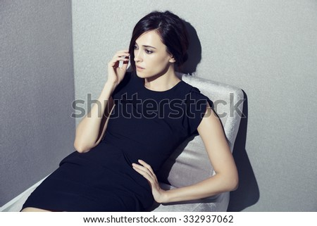 Fashion glamour female model in black dress portrait on the sofa in interior - stock photo