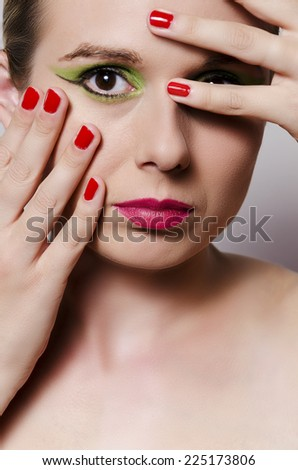 fashion glamour portrait of a blonde woman with heavy makeup holding fingers in front of her eye