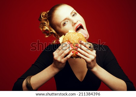 Fashion & Gluttony Concept. Happy red-haired model in black cocktail dress sticking out tongue & eating burger over red background. Perfect skin, make-up & manicure. Golden accessories. Studio shot - stock photo