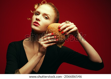 Fashion & Gluttony Concept. Portrait of luxurious red-haired model in black cocktail dress eating burger over red background. Perfect hair, skin, make-up and manicure. Golden accessories. Studio shot