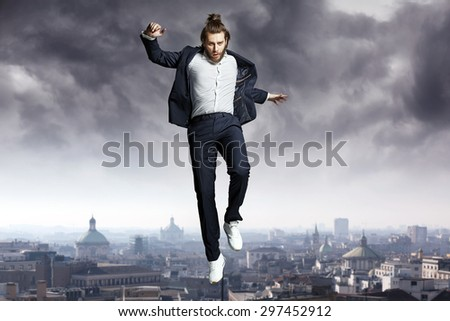 Fashion guy jumping to the sky - stock photo