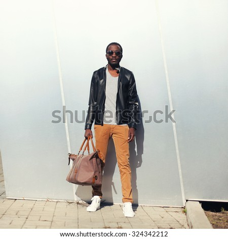Fashion handsome african man model wearing a sunglasses and black rock leather jacket with bag in city