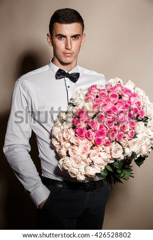 Fashion handsome brunette man model  with gorgeous roses bouquet, stylish macho male with  bow tie studio shot, handsome young man model isolated on beige, luxury life man, series - stock photo