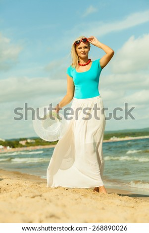 Fashion, happiness and lifestyle concept. Lovely blonde girl in full length with hat in hand red sunglasses and summer clothing walking on beach. Young woman relaxing on the sea shore.