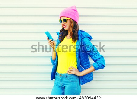 Fashion happy cool smiling girl using smartphone in colorful clothes over white background wearing a pink hat yellow sunglasses and blue jacket