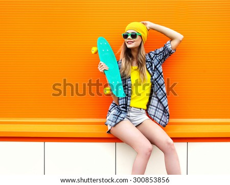 Fashion happy smiling hipster cool girl in sunglasses and colorful clothes with skateboard having fun outdoors against the orange background - stock photo