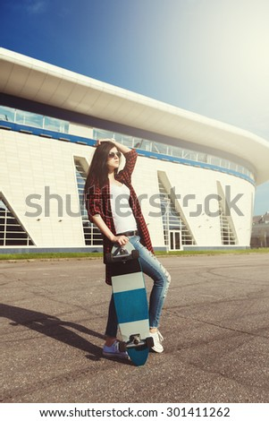 Fashion Hipster Girl in Sunglasses With Skateboard. Sunset Soft Light Vintage Effect Photo