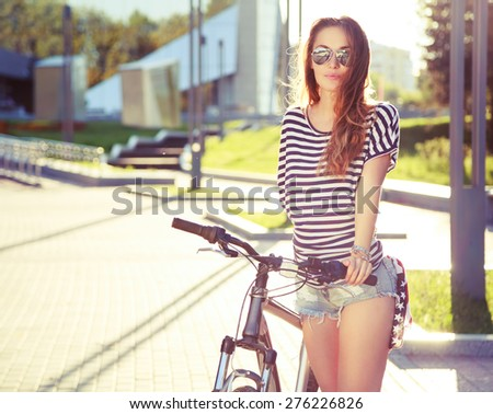 Fashion Hipster Woman with Bicycle in the City. Toned and Filtered Photo. Modern Youth Lifestyle Concept. - stock photo