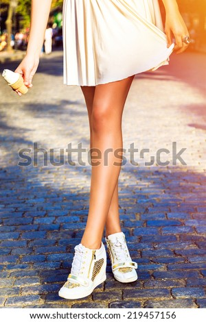 Fashion image of perfect long slim woman legs, posing at the street at european city,at mini white skirt and trendy sneakers, holding cone ice cream on had hand.Instagram bright fall colors. - stock photo