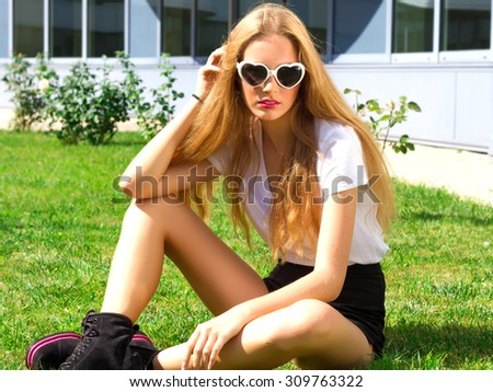 Fashion image of stylish hipster woman wearing black shorts, white t-shirt, sunglasses and boots.Green grass background, bright colors. - stock photo